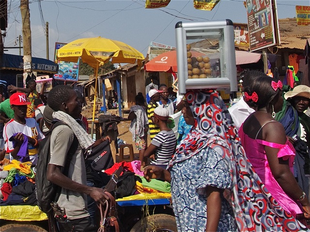 Woman carrying a plastic box of eggs on her head through a market.